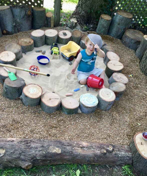 Child playing in a woodwares playscape sandbox with excess wood from Town Branch Tree Experts